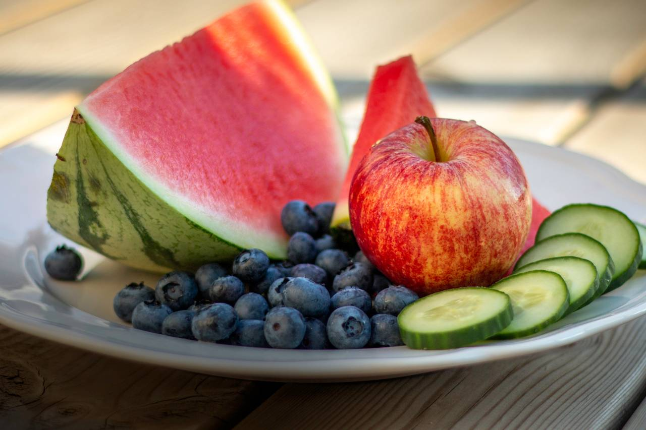 Et smakfullt fruktfat med saftige meloner, epler, agurker og blåbær. Du får vann i munnen av å se på bildet.
