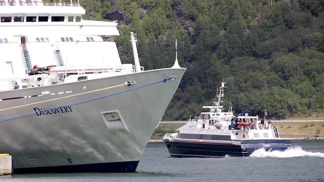 Medan dei fleste fjordarmane i Sogn og Fjordane har svært liten båttrafikk er det til tider hektisk aktiviet på Aurlandsfjorden. Her forlet snøggbåten Fjordprins Flåm. Ved cruisekaia ligg turistskipet Discovery. Foto: Steinar Lote, NRK.