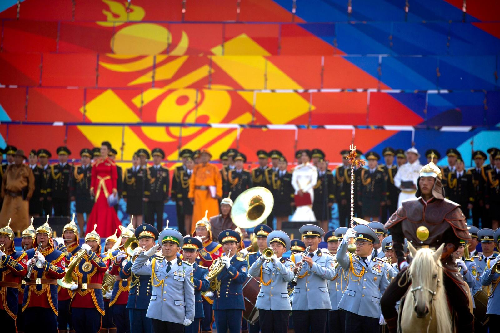 """Et korps marsjerer foran et gigantisk mongolsk flagg under Naadam-festivalen i Mongolia den 11 juli. Under festivalen konkurreres det i mongolsk bryting, hesteløp og bueskyting. I Mongolia blir festivalen også kalt """"eriin gurvan naadam"""", som betyr """"menns tre leker""""."""
