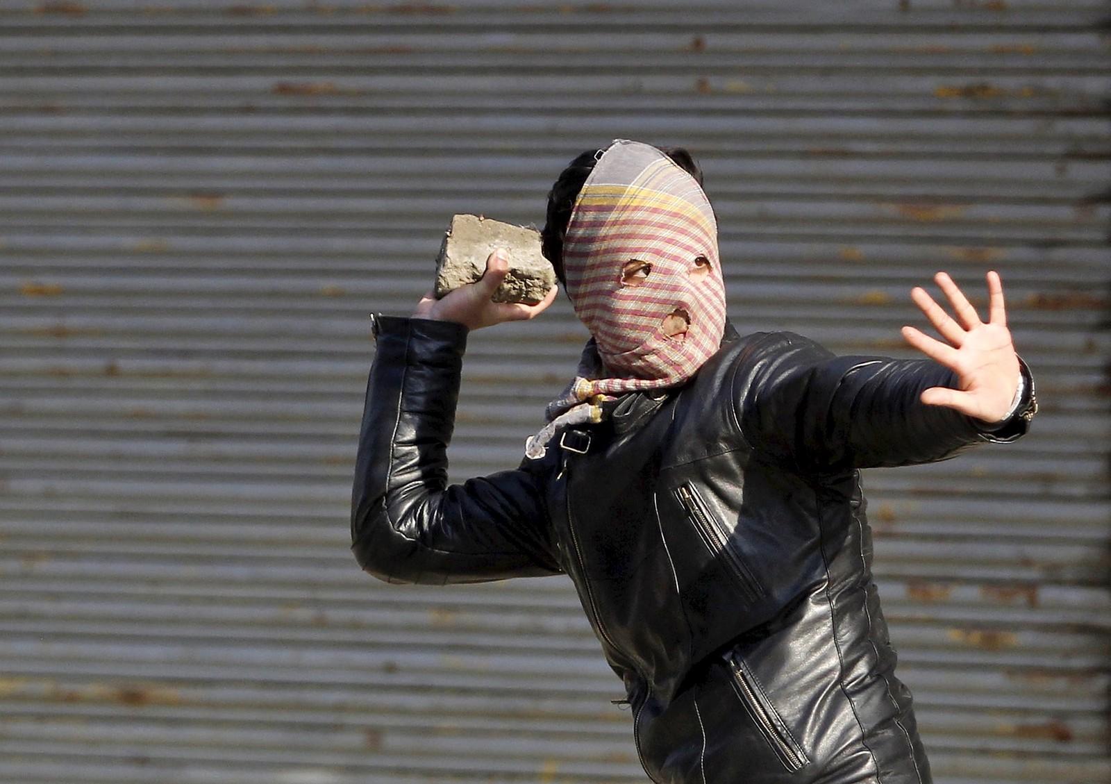 En maskert person kaster stein mot politiet under en demonstrasjon i den indiske byen Srinagar.