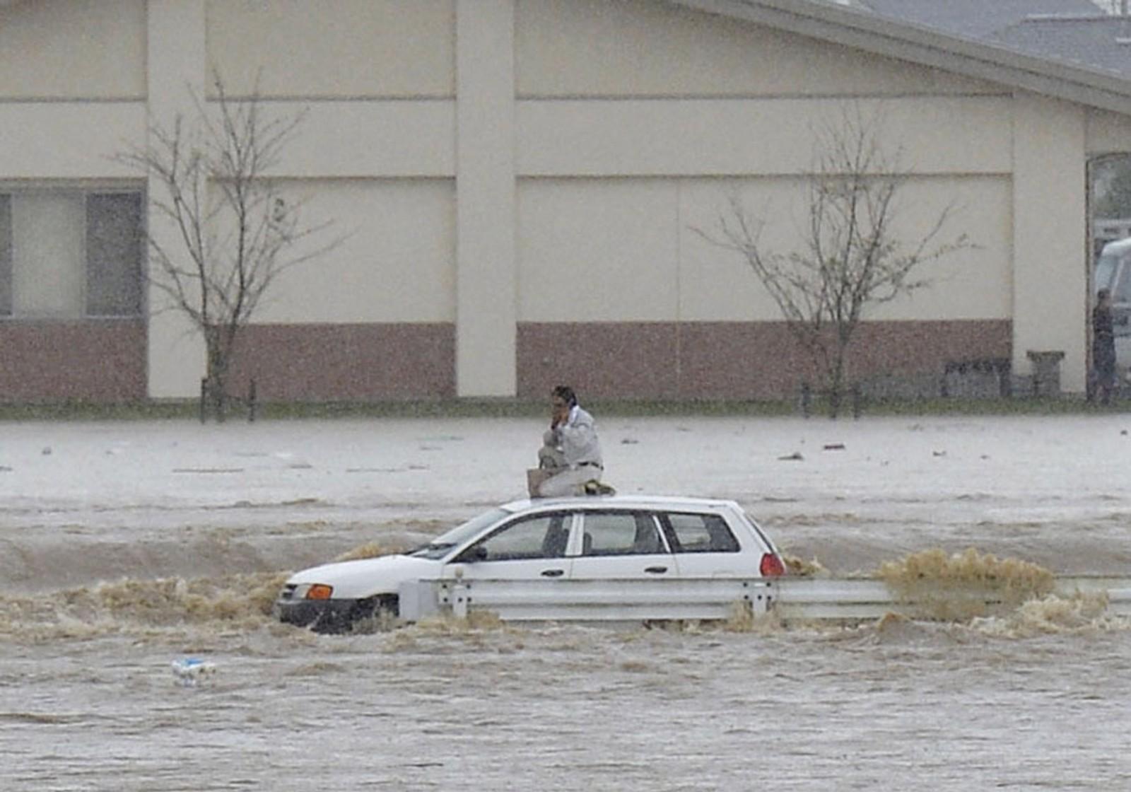 Denne mannen måtte sette seg på taket av bilen sin under en voldsom flom i Kinugawa-elva i Japan denne uka.