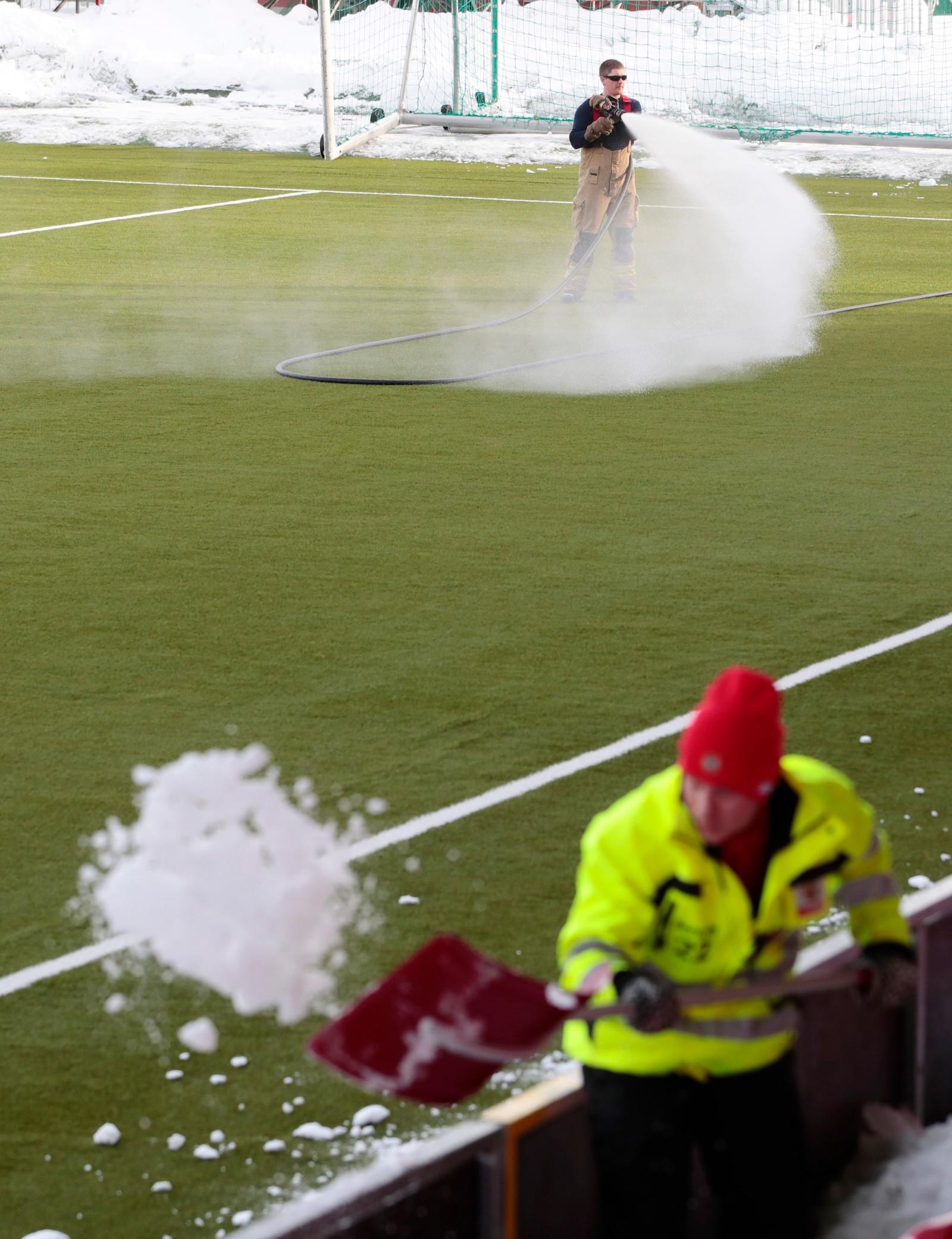 Brannvesnet sprøyter varmt vann på kunstgresset og banemannskaper rydder tribunen for snø før eliteseriekampen i fotball mellom Tromsø og Brann på Alfheim Stadion.