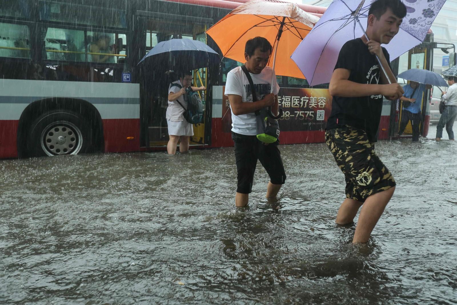 Selv om paraplyene beskytter for regnet er det ikke lett å komme seg tørrskodd frem i Beijing