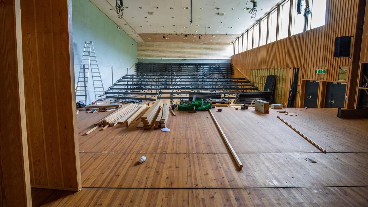 En aula demonteres, bare understellet står igjen. Alle setene er borte. Bildet er tatt fra scenen, og man ser ut i rommet. På scenen ligger det verktøy og planker i stabler.