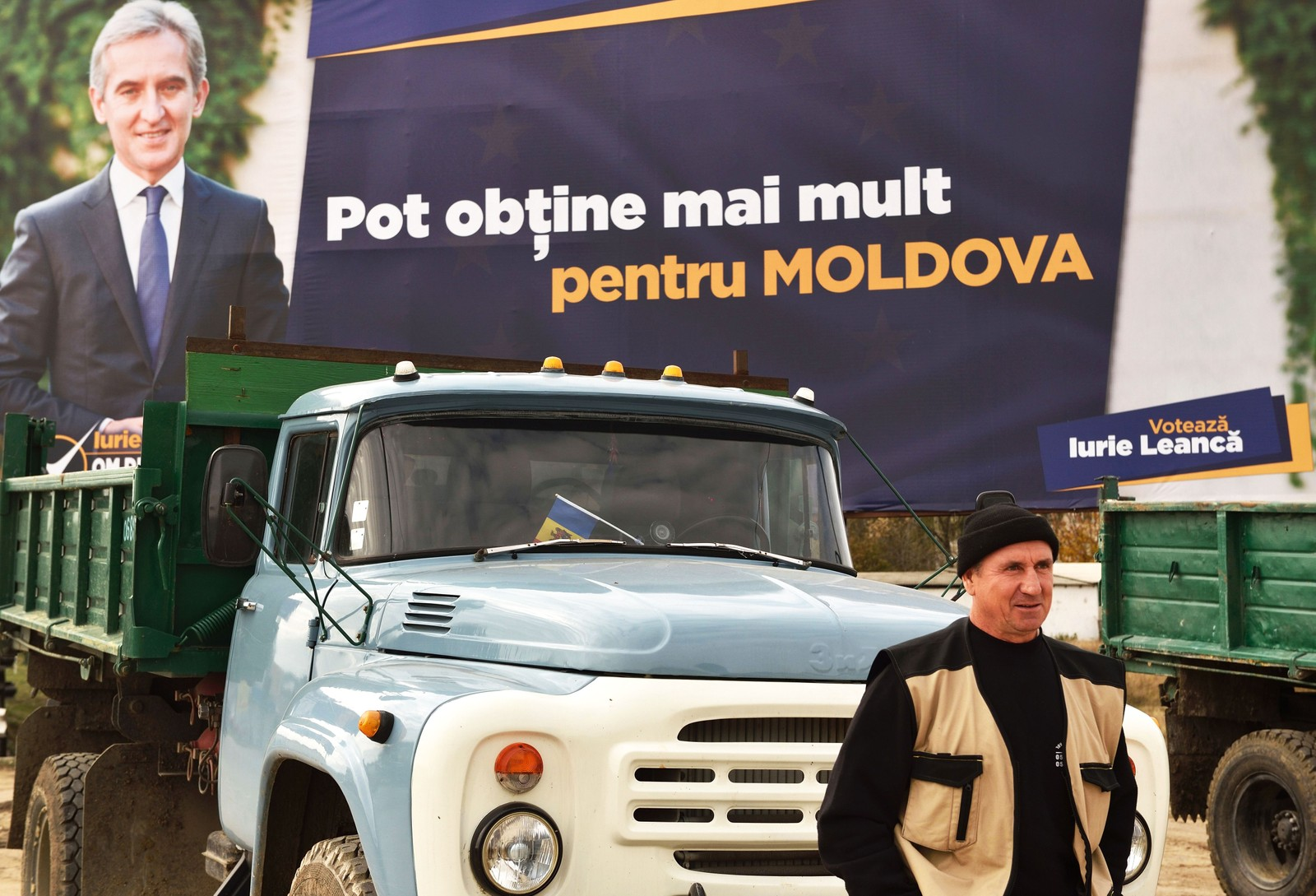Arbeidsløsheten er høy på landsbygda i Moldova. En mann står og venter på arbeid i Hancesti, mens presidentkandidat Iurie Leanca smiler på en plakat i bakgrunnen.