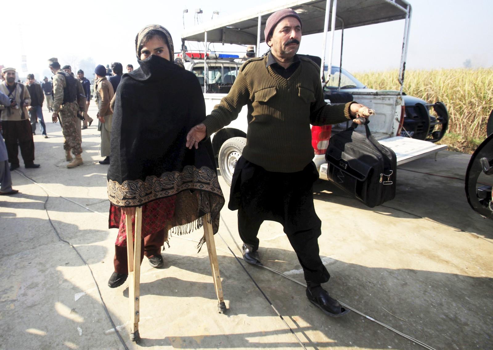 En kvinnelig lærer med krykker hjelpes bort fra Bacha Khan-universitetet i Chasadda