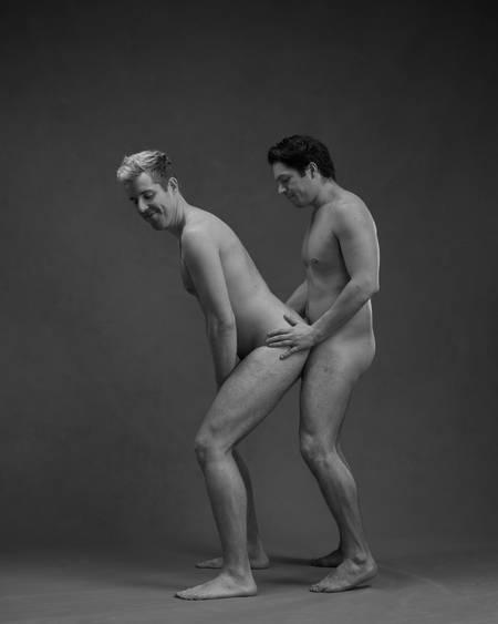 En naken mann står på gulvet med rumpa ut mot en annen naken mann som står bak ham og holder han på hoftene