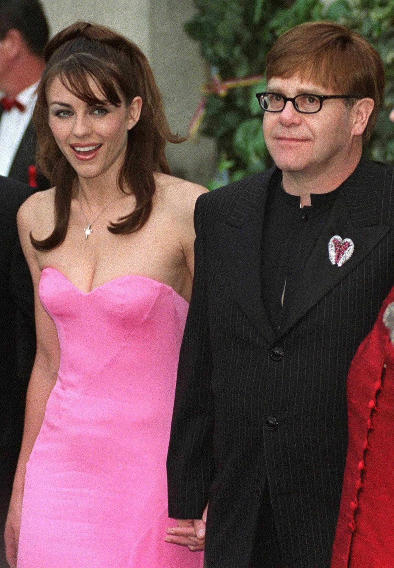 1998: Hand i hand kjem den britiske skodespelaren Elizabeth Hurley og Elton John til AMFAR (American Foundation for AIDS Research) veldedighetsmiddag på Moulin de Mougins restaurant i Frankrike 21. mai.
