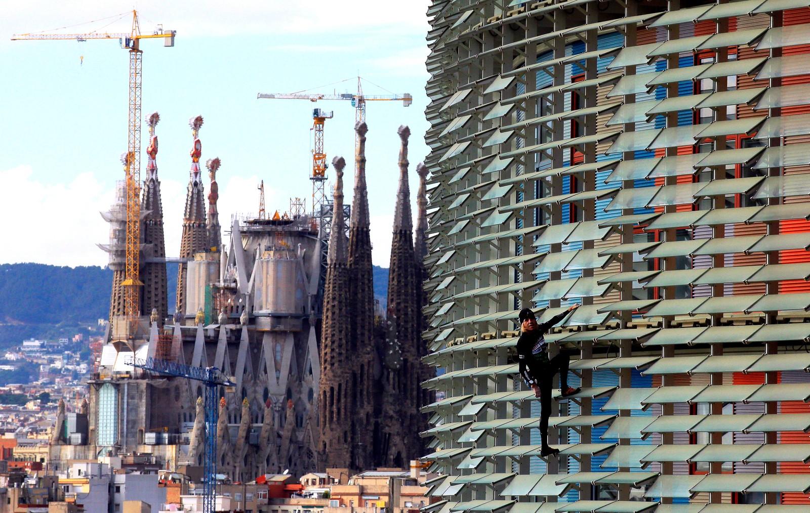 Den franske klatreren Alain Robert, er på vei opp det 145 meter høye Agbartårnet i Barcelona. I bakgrunnene ser vi La Sagrada Familia.