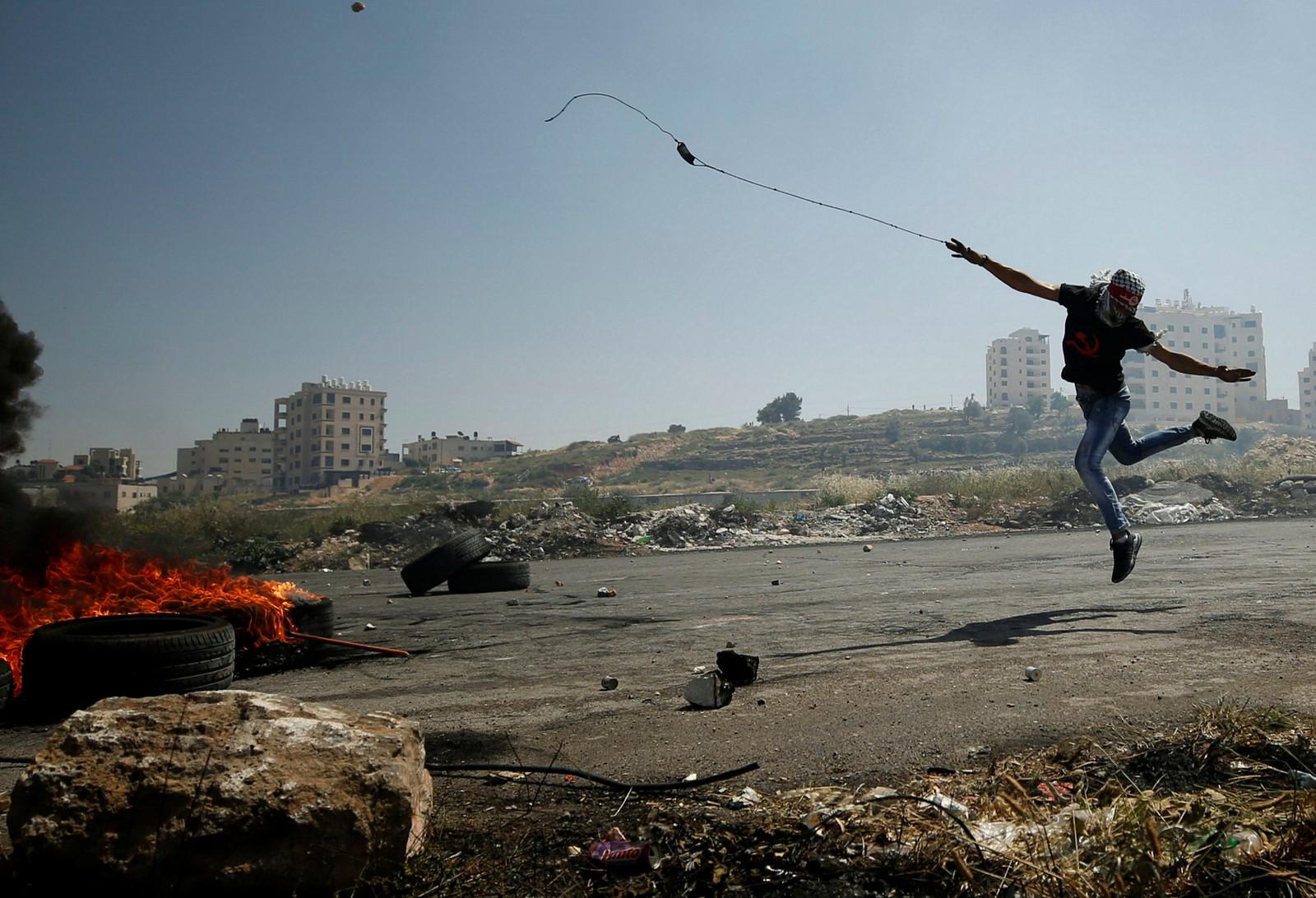 En palestinsk demonstrant slynger stein mot israelske tropper.