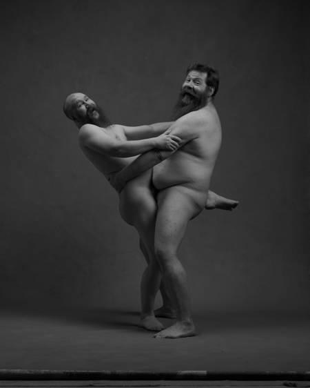 En naken mann med skjegg står på gulvet og holder rundt hoftene til en annen naken mann med skjegg som har det ene bene rundt den andres hofter.