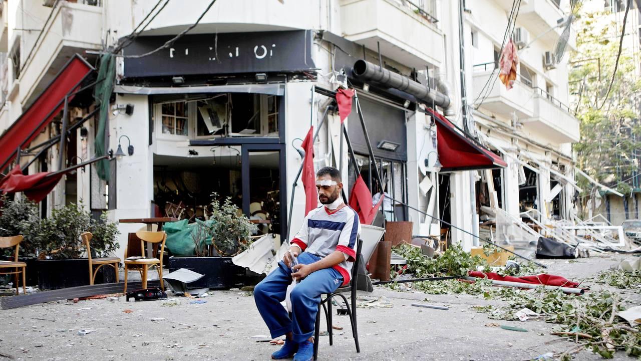 En skadet mann sitter utenfor en ødelagt restaurant etter eksplosjonen