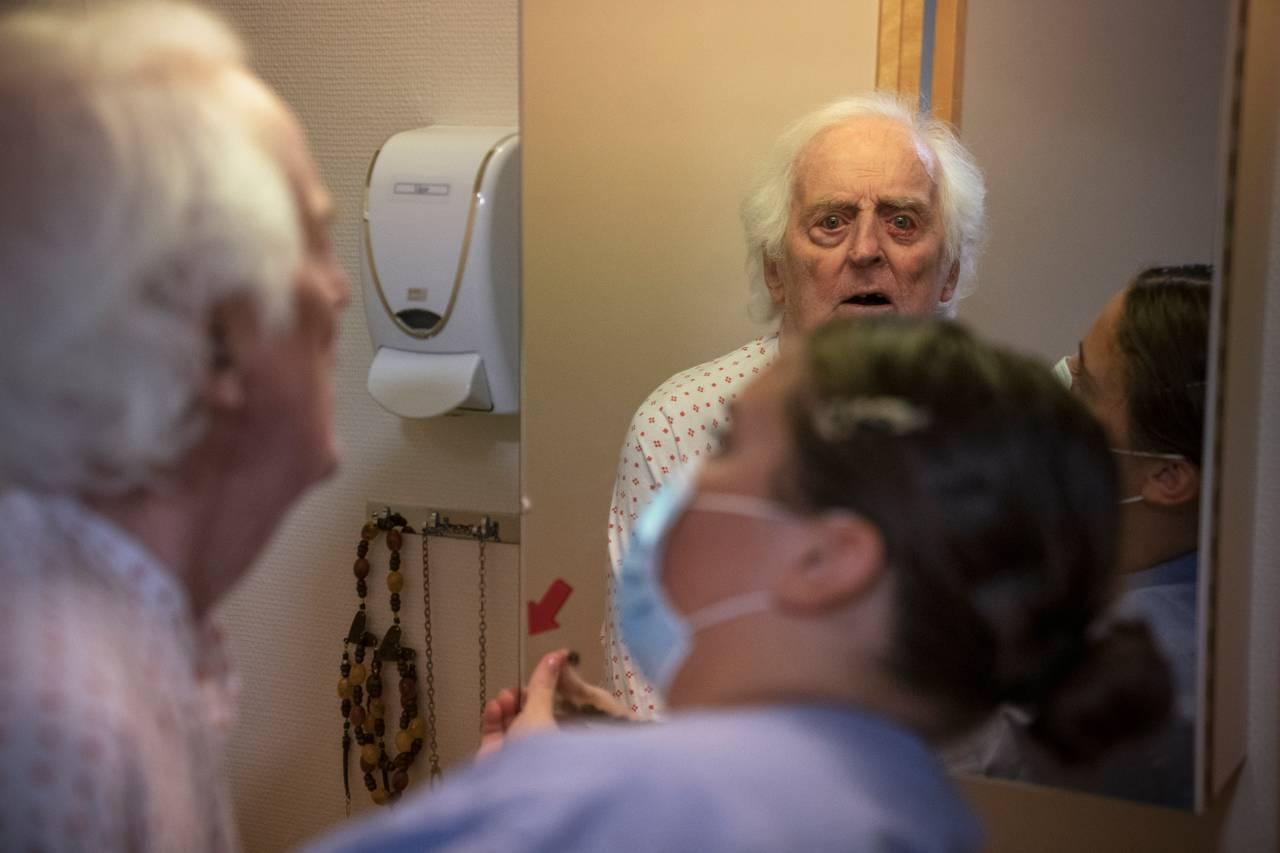 Birger stirrer forvirret inn i speilet mens en pleier forsøker å hjelpe han.