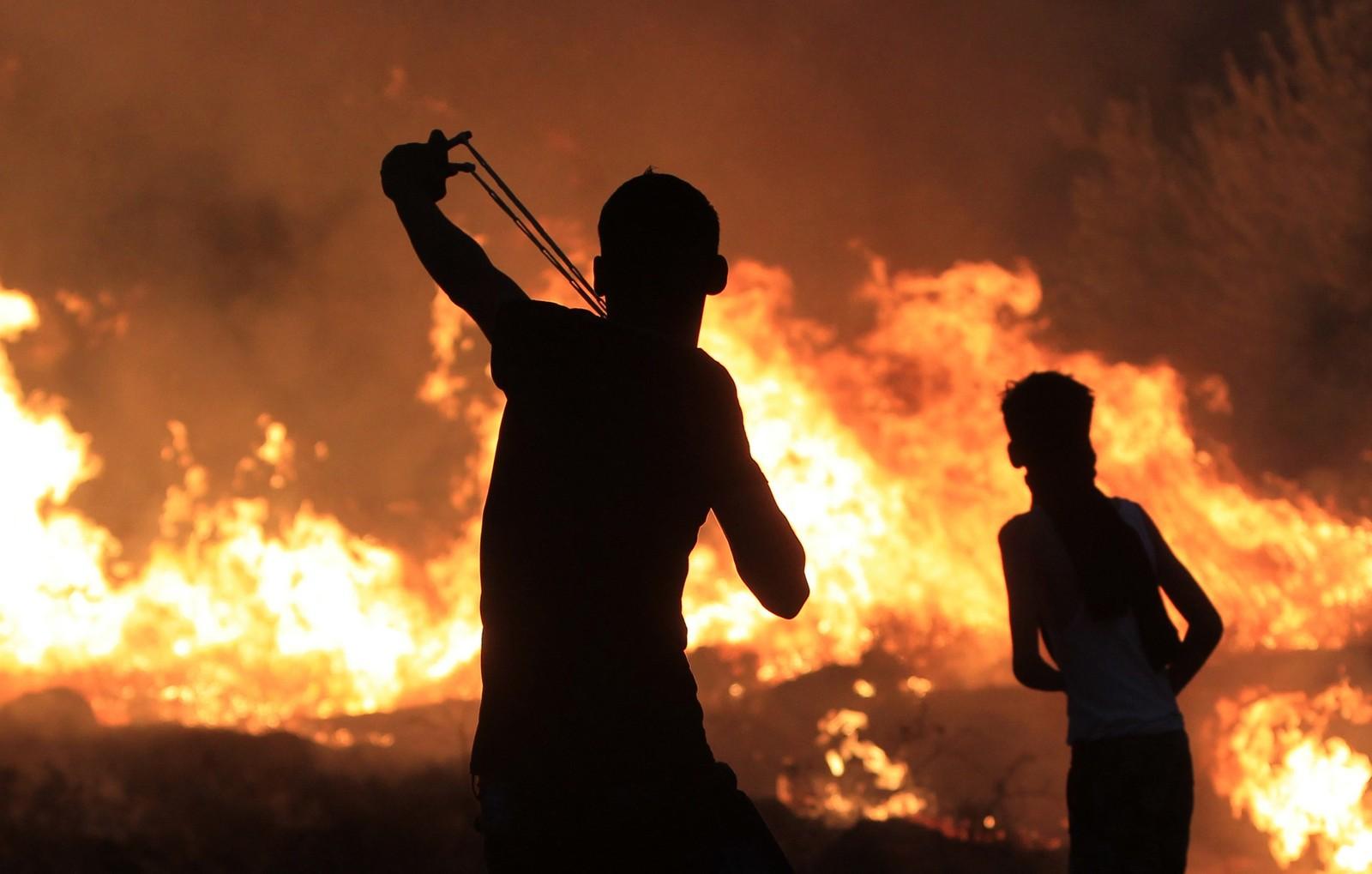 En palestiner bruker en sprettert under en konfrontasjon med Israelske sikkerhetsstyrker. Palestinerne protesterer som en reaksjon på at et 18 måneder gammelt barn ble drept i et israelsk angrep tidligere denne uken.