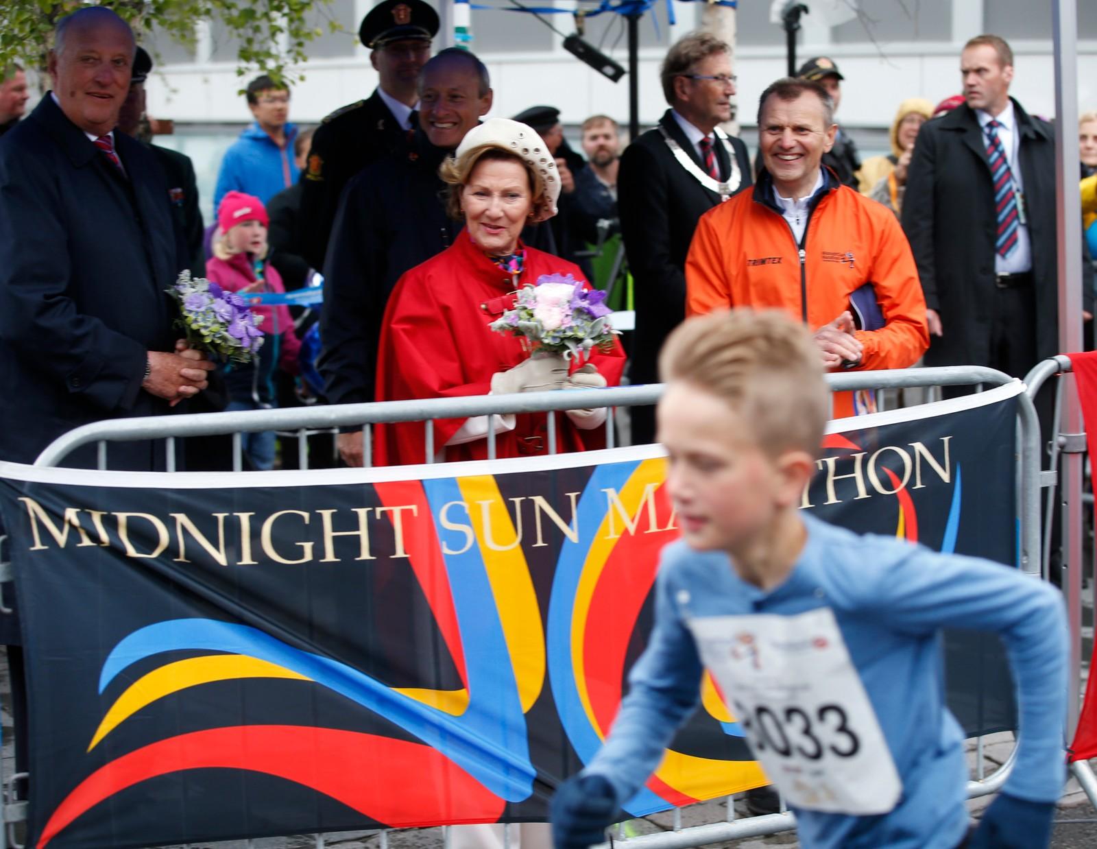 Kong Harald og dronning Sonja deltar på folkefesten på Stortorget og overværer Labb og Line-barneløpet lørdag. Reisen inngår som en del av markeringen av Kongeparets 25-årsjubileum. Nils Hætta (orange), leder av Midnight Sun Marathon tar imot kongeparet. Foto: Lise Åserud / NTB scanpix
