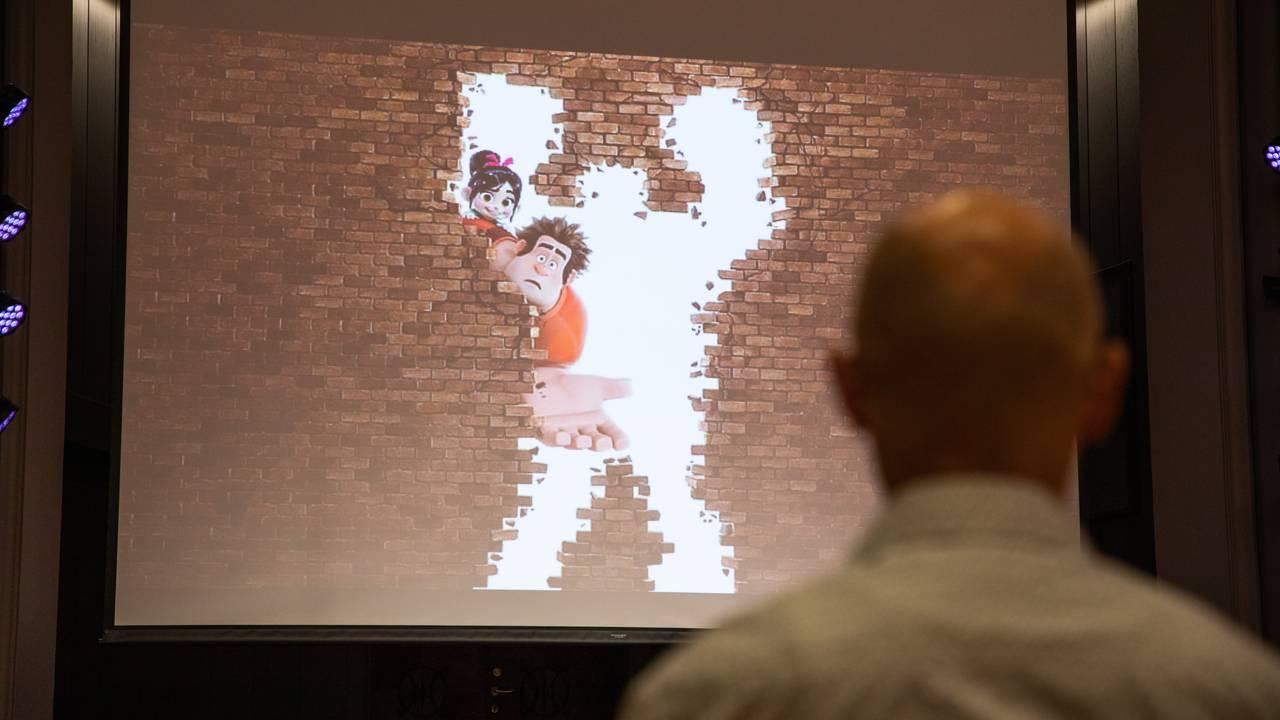 I bakgrunn ser man et bilde av animasjonsfiguren Rive-Rolf fra filmen med samme navn. I forgrunnen ser man ryggen til Svein Egil Dagsland som ser mot skjermen.
