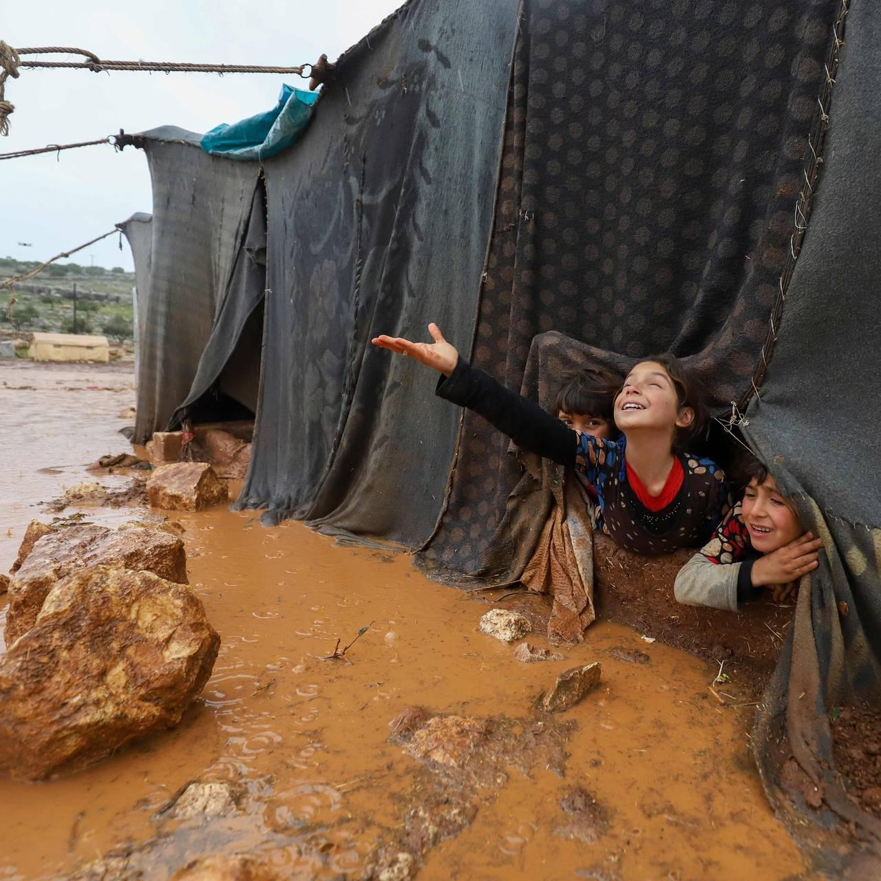Barn leker etter kraftig regnvær har rammet en teltleir i Idlib-provinsen.
