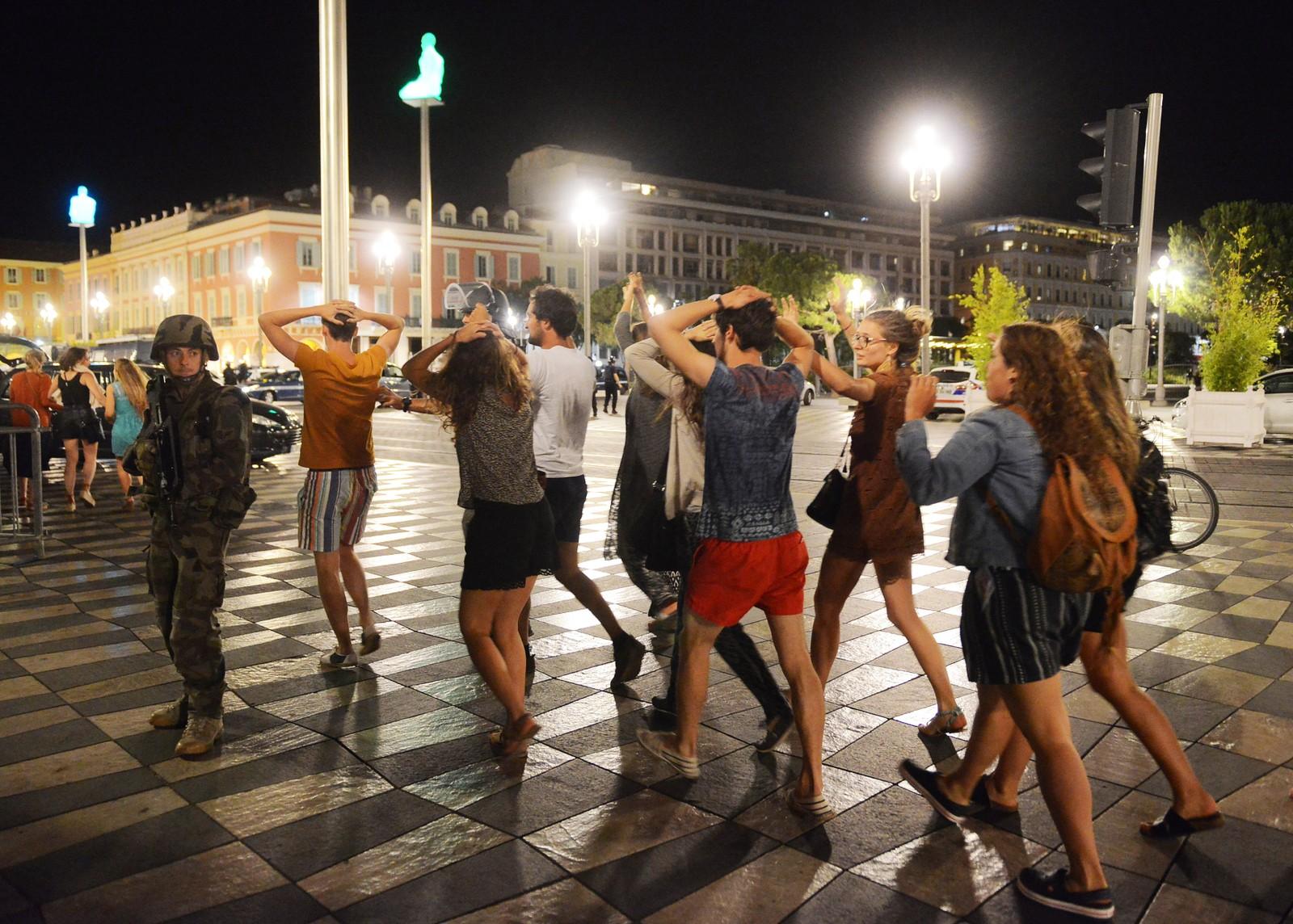 Terrorangrep i Nice 14. juli 2016: Sivile krysser gaten med hendene over hodet mens en soldat passer på.