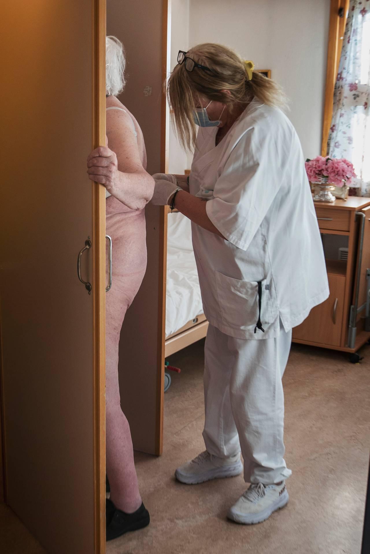 En naken kvinne står skjermet bak en dør og får hjelp av en pleier til å ta på seg BHen