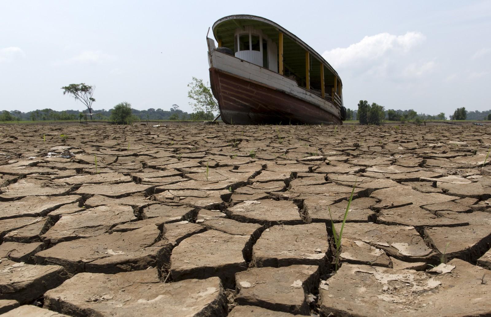 En båt står på bunnen av en del av Amazonas-elva ved byen Manaus i Brasil. Tørke har ført til at flere tusen slike båter skal ha stranda på bunnen.