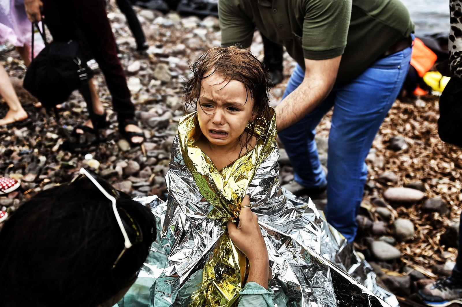 En syrisk pike gråter etter å ha fått en varmeteppe rundt seg rett etter å ha kommet i land på Lesvos 28. september 2015.