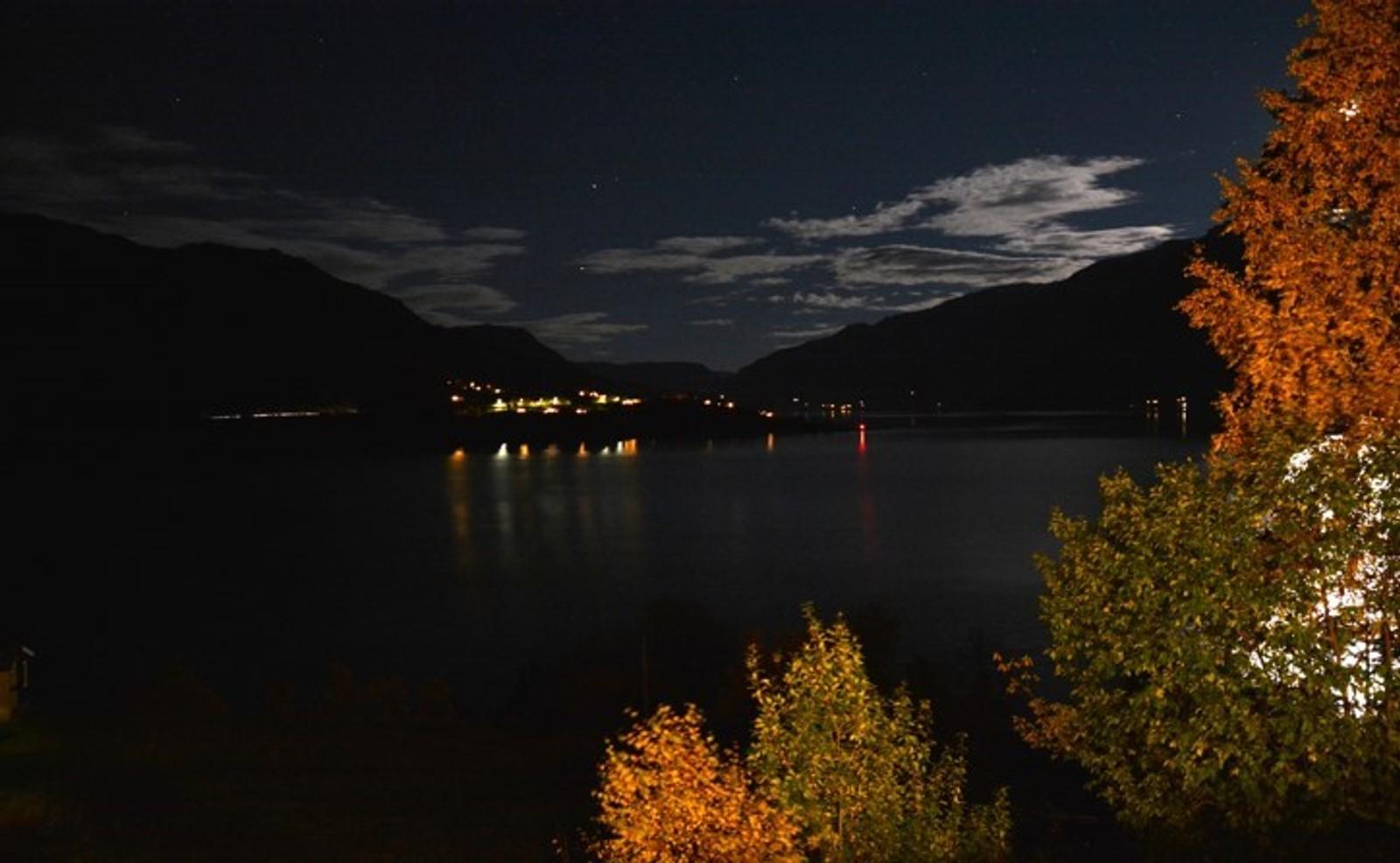 Fra Eikjastrondi mot Nes og Lustrafjorden. Månen tittar fram til høgre bak haustgult lauv.