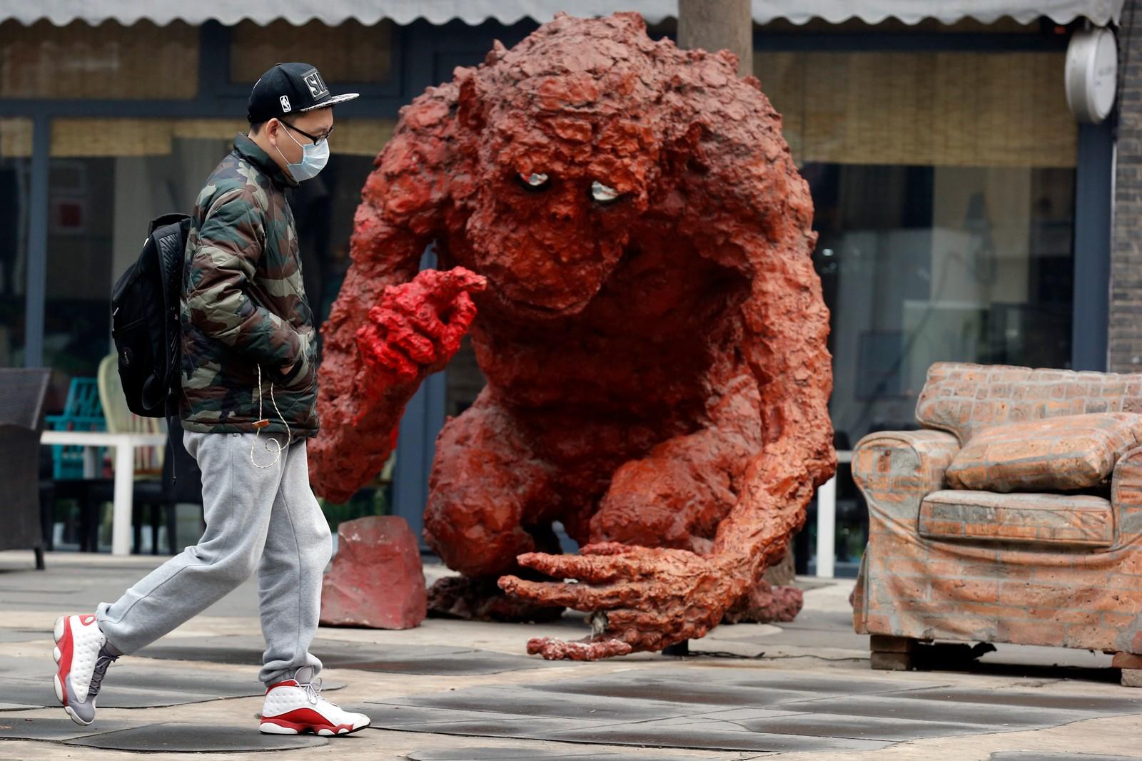 En mann sverger til munnbind når han er ute og går i den forurensede luften i kinas hovedstad Beijing.