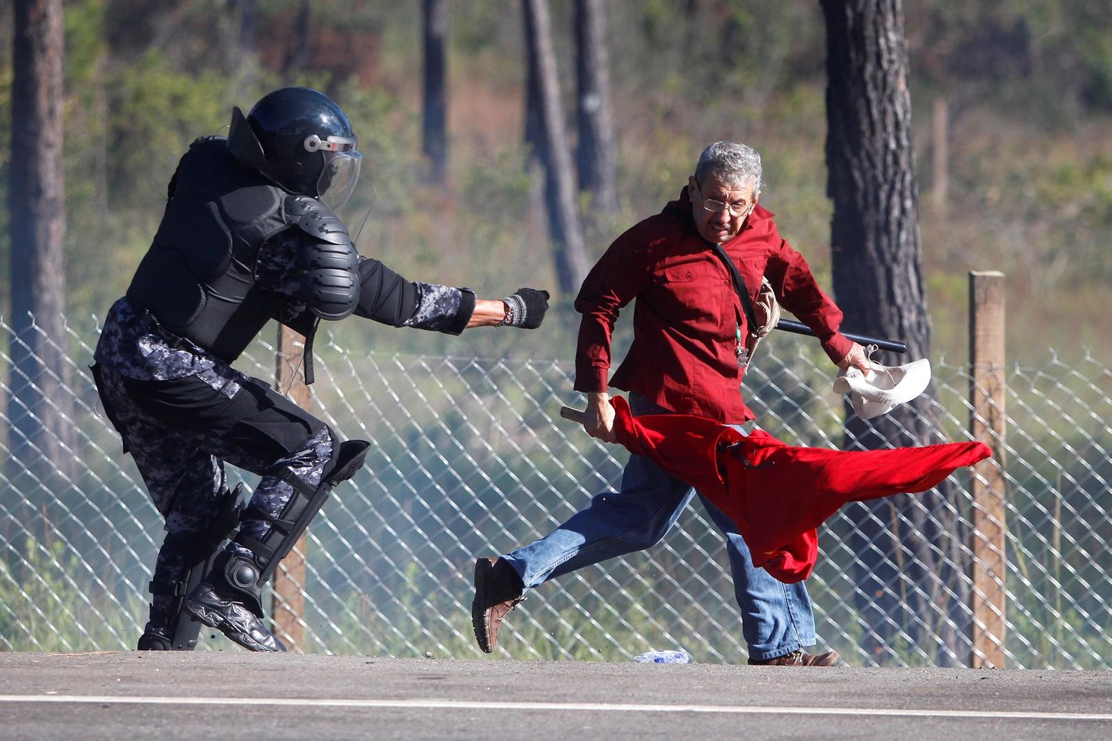 En politimann jager en demonstrant i Honduras den 3. oktober. Det var store demonstrasjoner i hele landet etter gjenvalget av president Juan Orlando Hernandez.