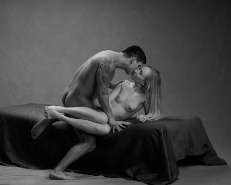 En naken dame ligger sidelengs på senga mens hun kysser en naken man med tatoveringer som står på kne bak rumpa hennes