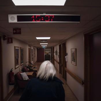Foto av en pasient som beveger seg nedover den mørke gangen på hjemmet.