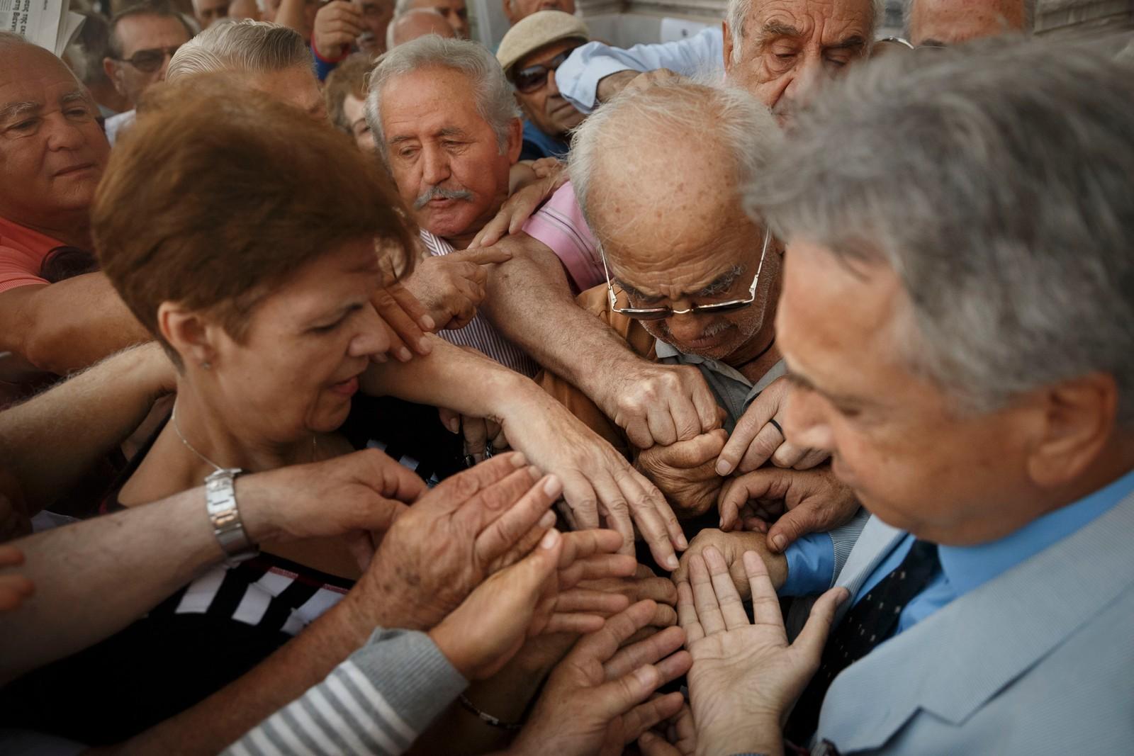 Pensjonister forsøker å få fatt i en kølapp for å få komme inn i en bank i Aten og få tatt ut penger.