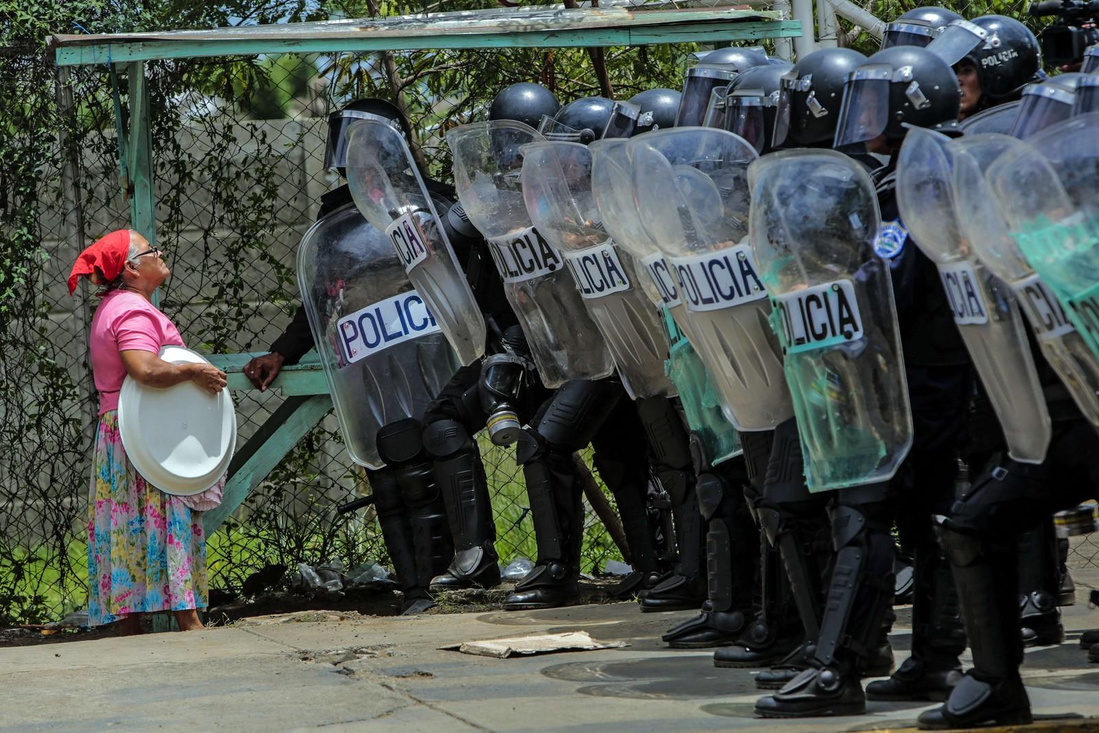 Opprørspoliti spør en eldre kvinne om tillatelse til å gå inn i huset hennes i Managua, Nicaragua. Politiet er på gatene grunna store demonstrasjoner i forbindelse med neste års valg.