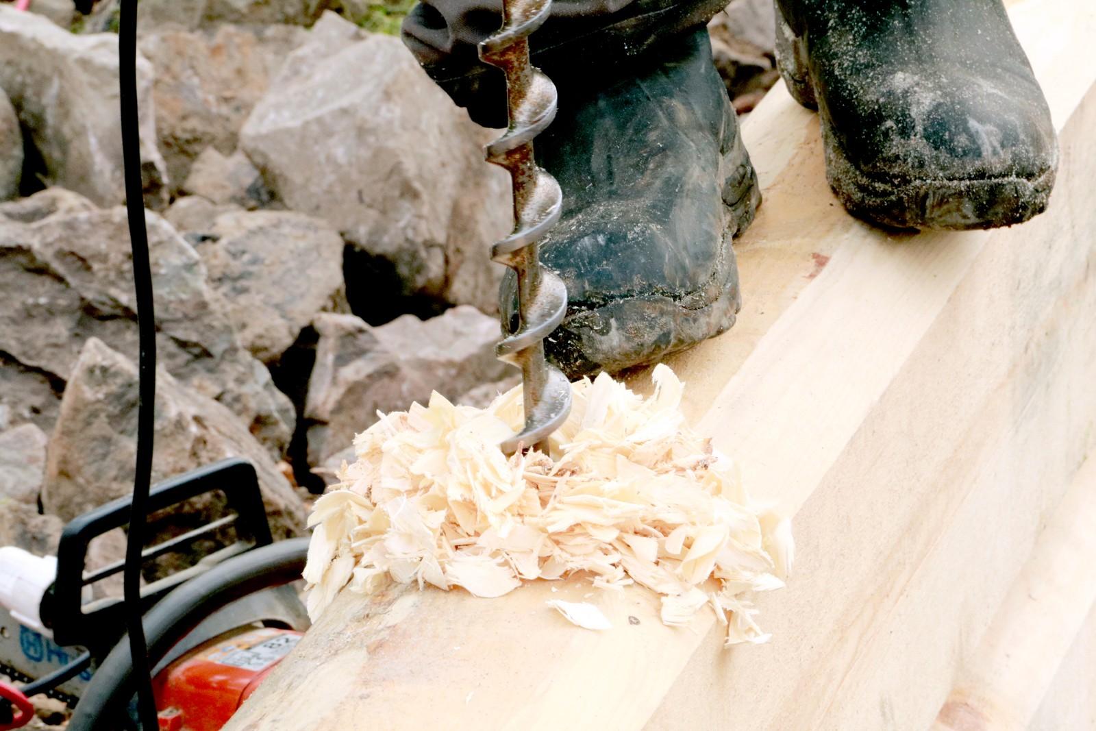 BORRER: Roar Gravermoen fra Fjell-Laft i Uvdal borrer hull i tømmerstokkene for å sette inn gjengestenger.