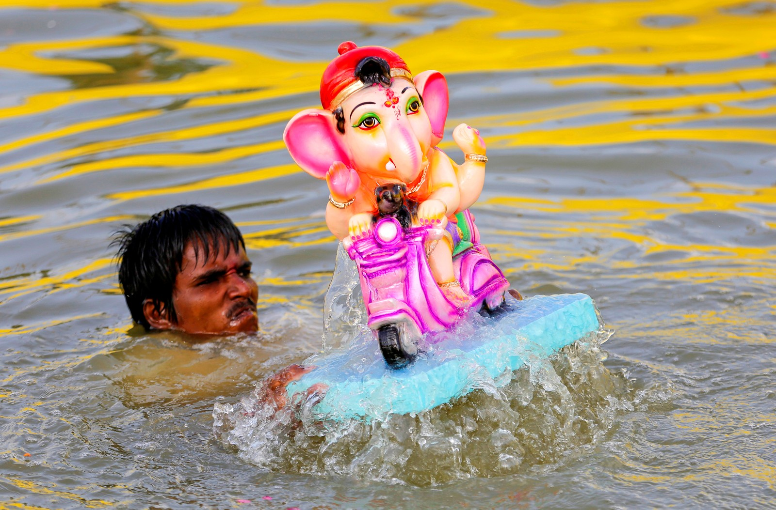 En mann senker et idol av Ganesh under den andre dagen av den hinduistiske festivalen Ganesh Chaturthi i Ahmedabad i India den 6. september.