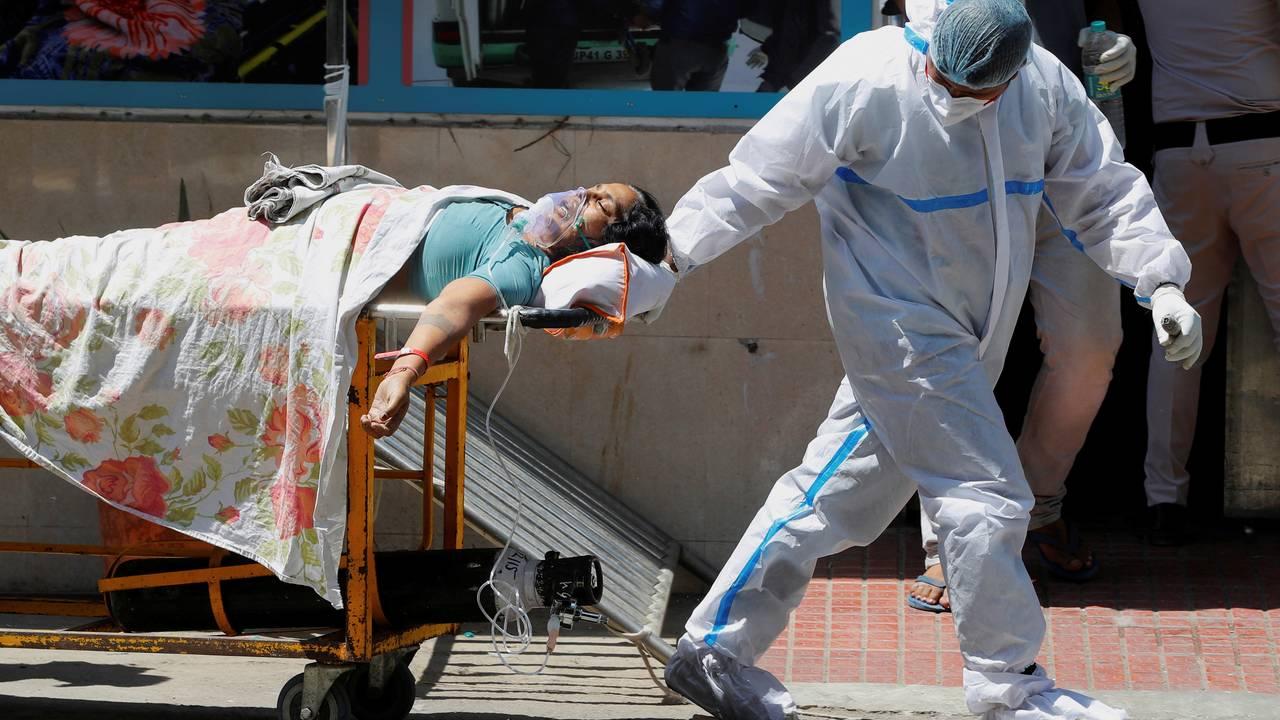 En helsearbeider trekker en covid-pasient etter seg mens sistnevnte får oksygen.
