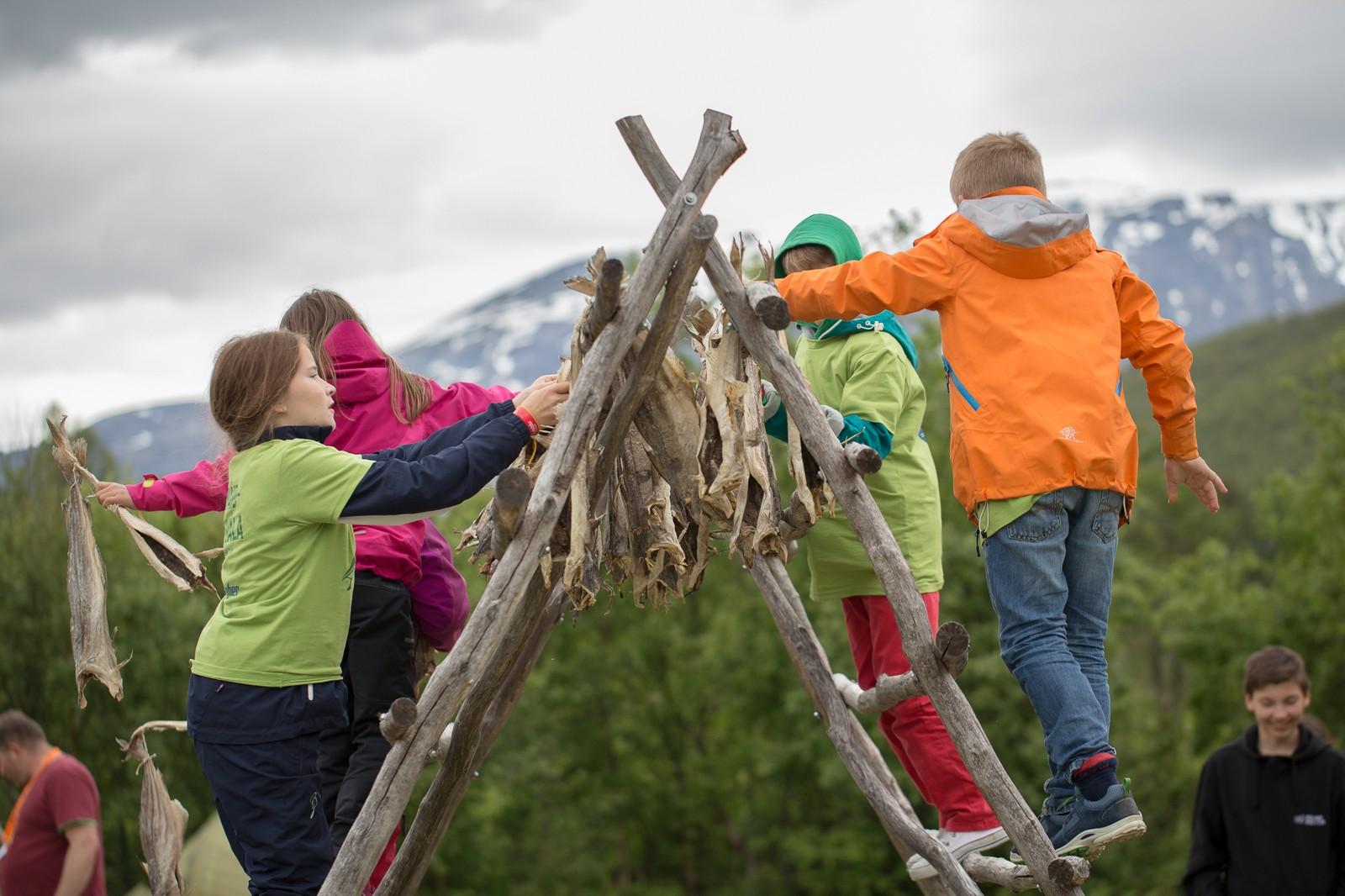Barna synes det var stas å få henge opp tørrfisk på hjellene.