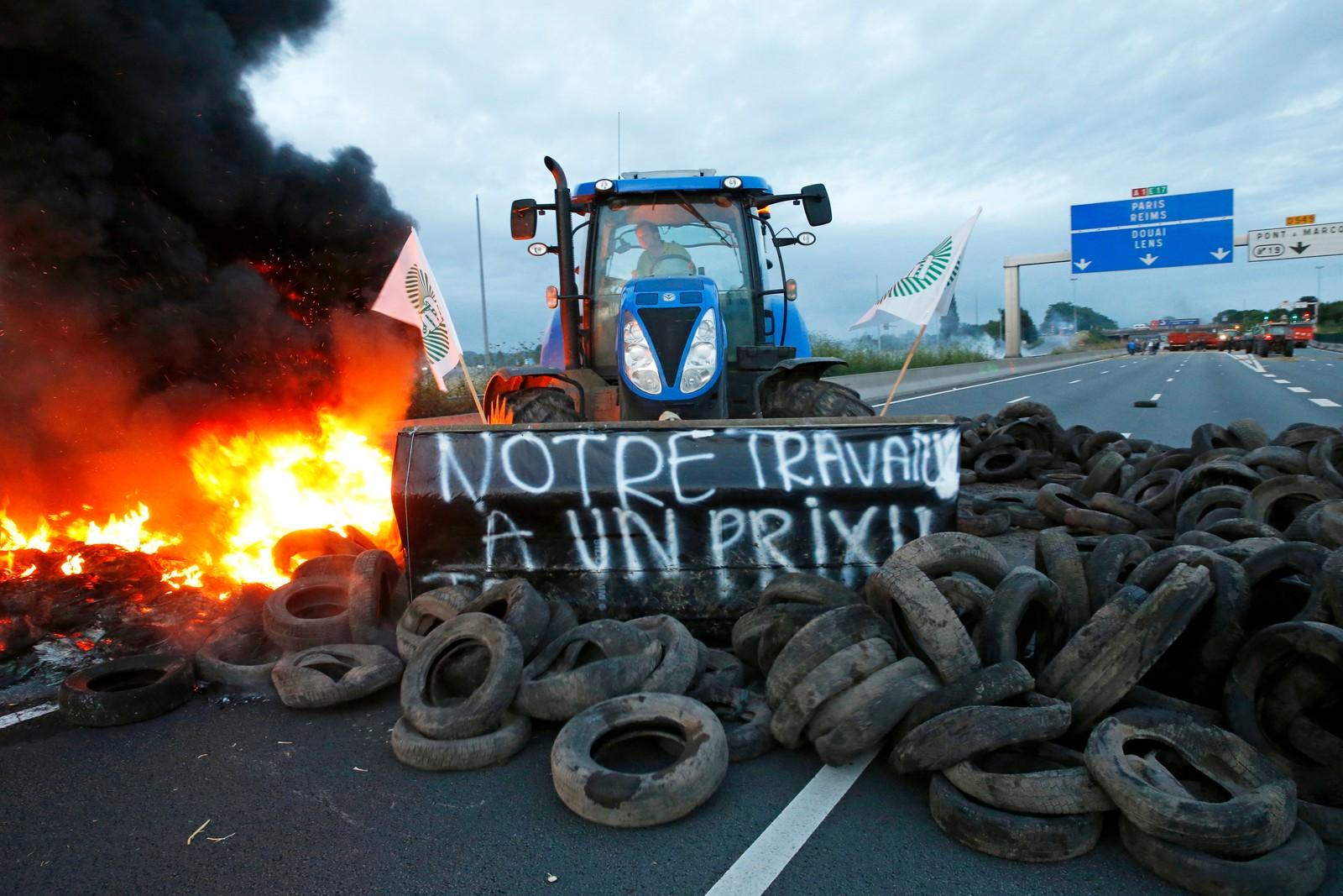 «Arbeidet vårt har en pris». En traktor dytter flere dekk på bålet på motorveien A1 mellom Lille og Paris onsdag.