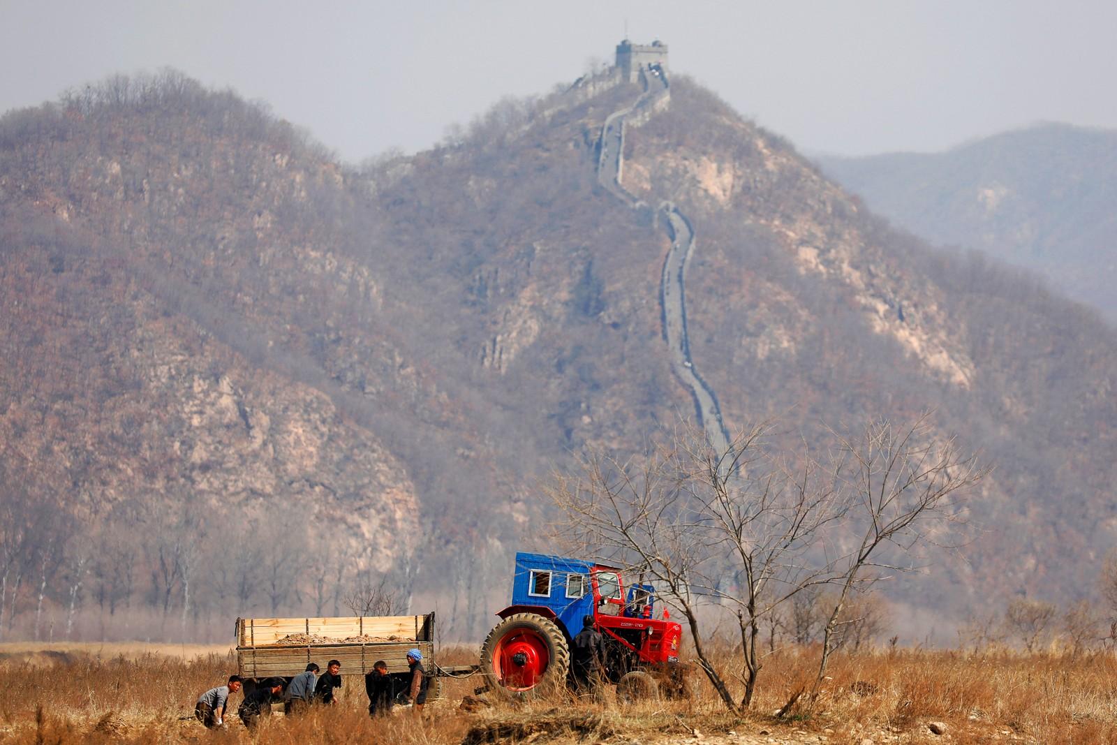 Nord-koreanske bønder jobber på en åker nord for byen Sinuiju. I bakgrunnen ser vi Den kinesiske mur.