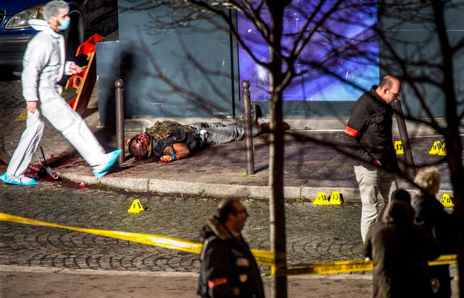 2. pris nyhet: Tre dager med terror i Paris er over. Angrepet mot satiremagasinet Charlie Hebdo var starten på et terrordøgn i Paris. Terroristen Amedy Coulibaly ligger drept på fortauet utenfor kosherbutikken Hyper Cacher. De tre terroristene drepte totalt 17 mennesker. Amedy Coulibaly ble begravet i en umerket grav i Paris. Juryens begrunnelse: Dette er «hardcore news». Fotografen er på rett sted til rett tid. Bildet er godt fordi fotografen har valgt å vise hele scenen. Terroristen som ligger død blir en del av miljøet og byen rundt. Vi blir også minnet på hvor viktig det er at fotojournalister dokumenterer slike hendelser. Historien kan ikke endres når det finnes fotografier.