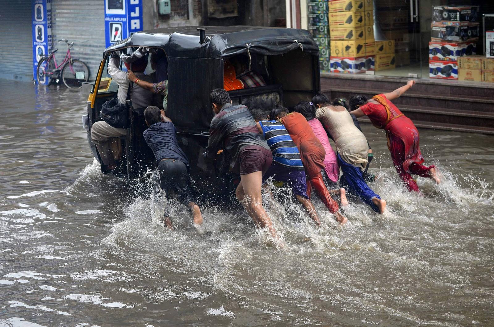 En rickshaw får hjelp av flere hender i den indiske byen Jalandhar.