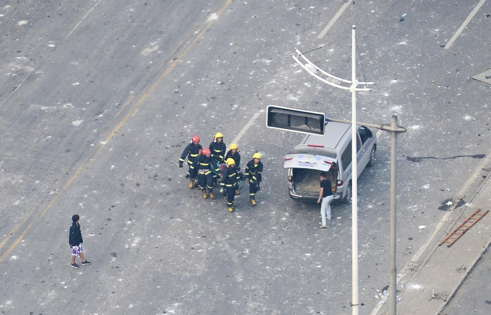 MINST 17 DØDE: Brannmenn bærer unna et offer for eksplosjonene.
