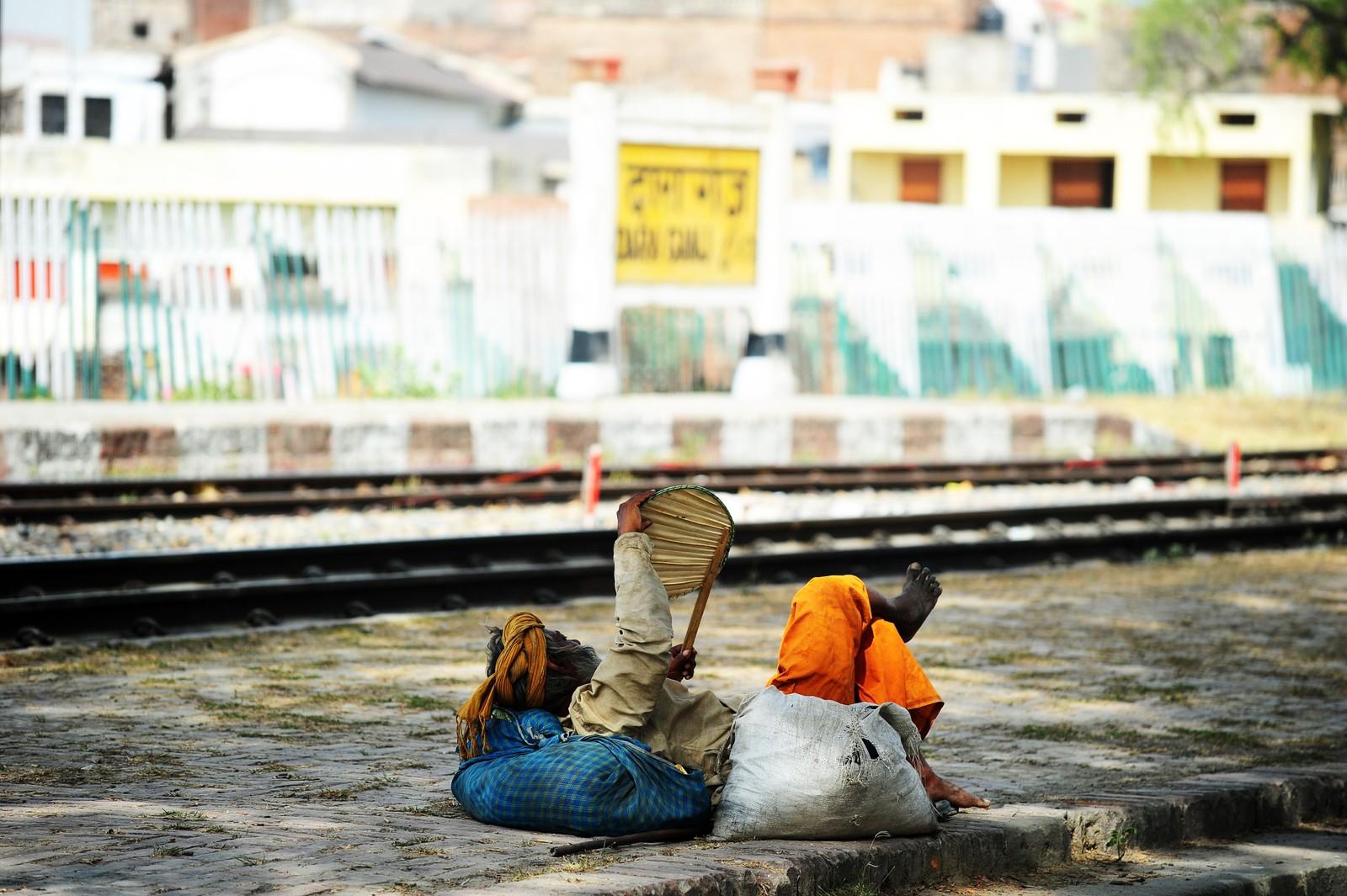 En mann kjøler seg ned med en vifte mens han venter på toget i Allahabad i India.