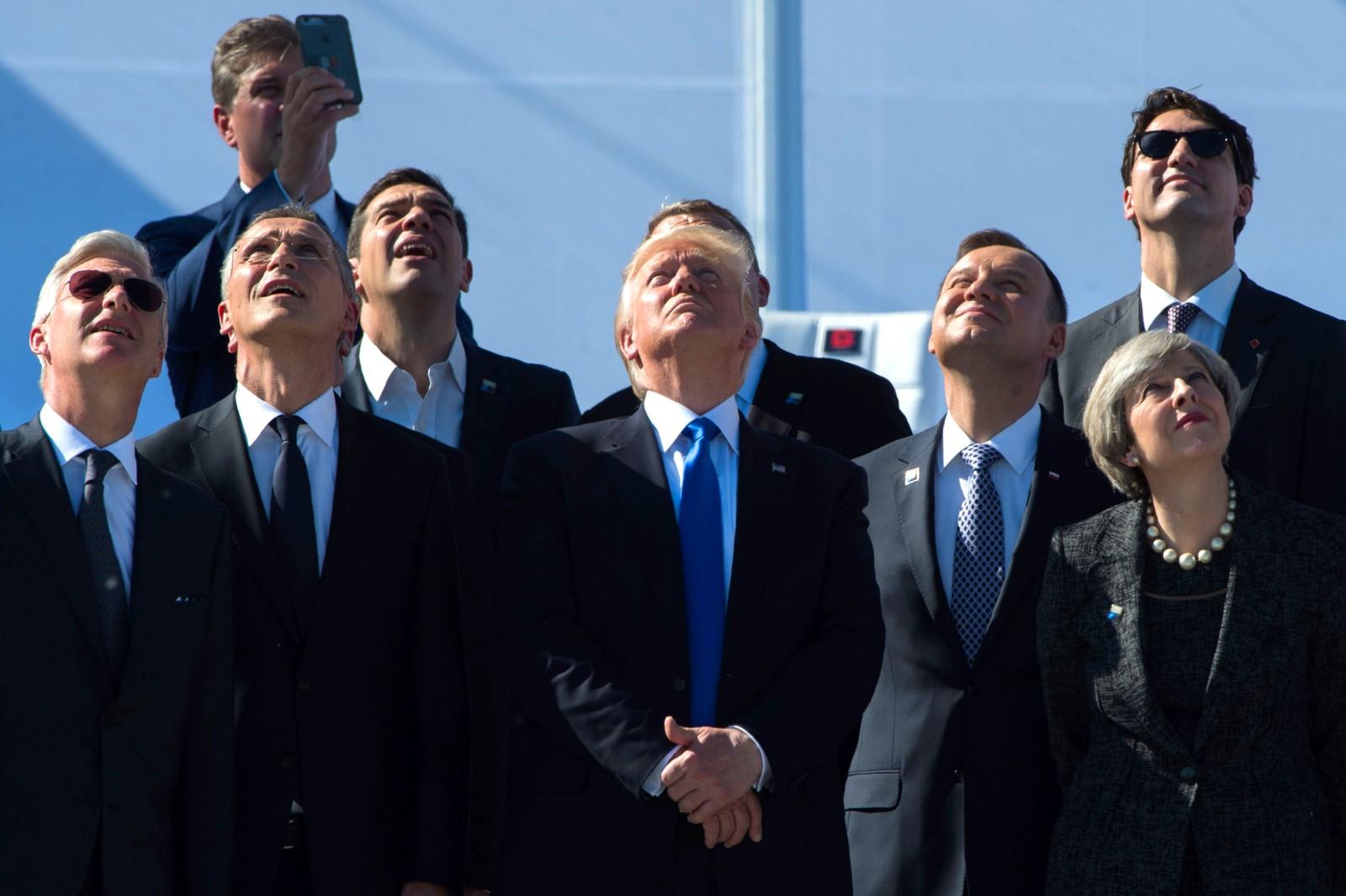 Også toppene må titte oppover noen ganger. Her ser den belgiske kongen Phillipe, Jens Stoltenberg, den greske statsministeren Alexis Tsipras, Donald Trump, Polens president Andrzej Duda, Storbritannias statsminister Theresa May og Canadas statsminister Justin Trudeau fly passere under åpningen av det nye NATO-hovedkvarteret.