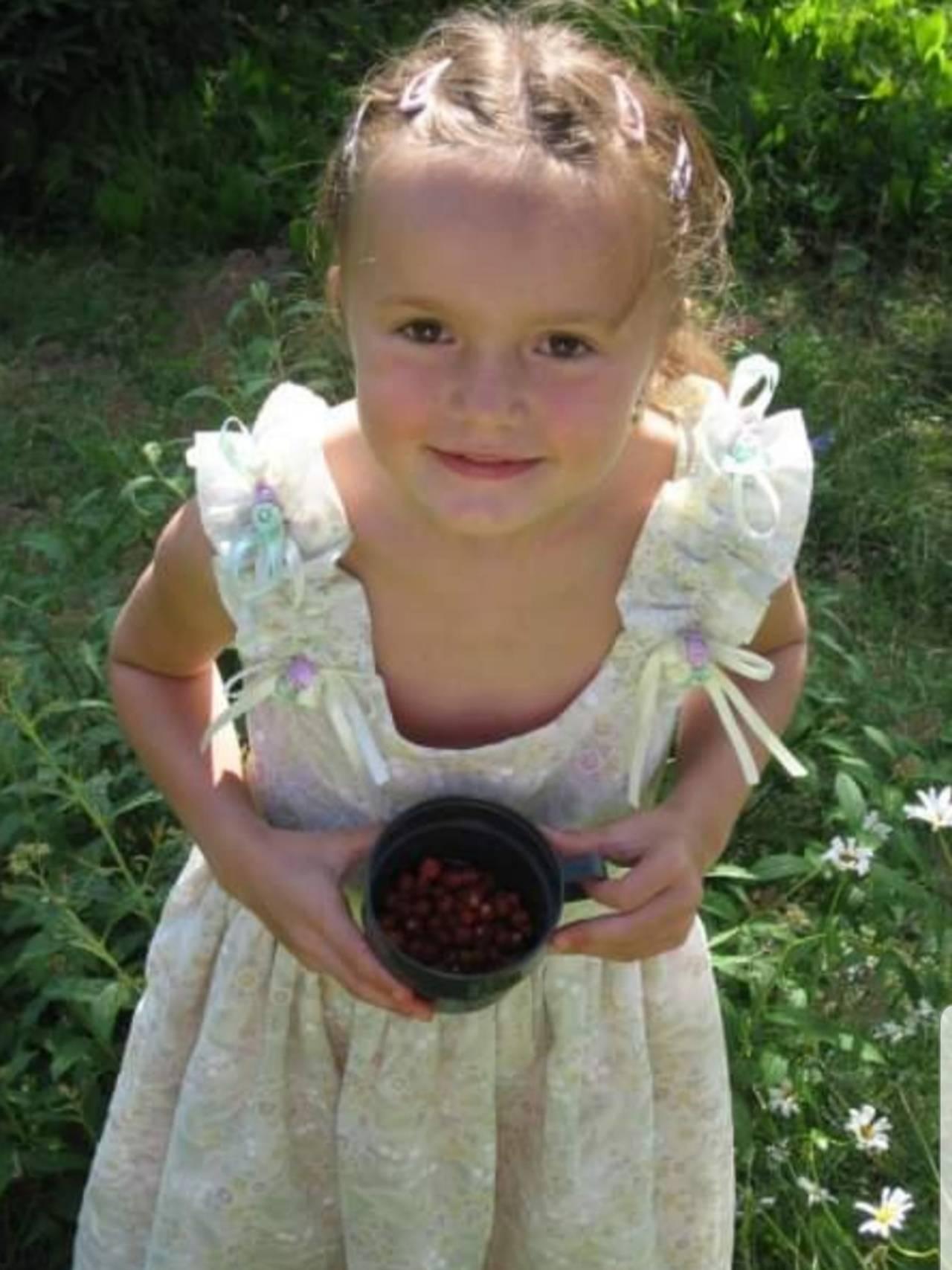 Andrine som barn står i en hage med blomstrete lys kjole og har plukket bær i en kopp.