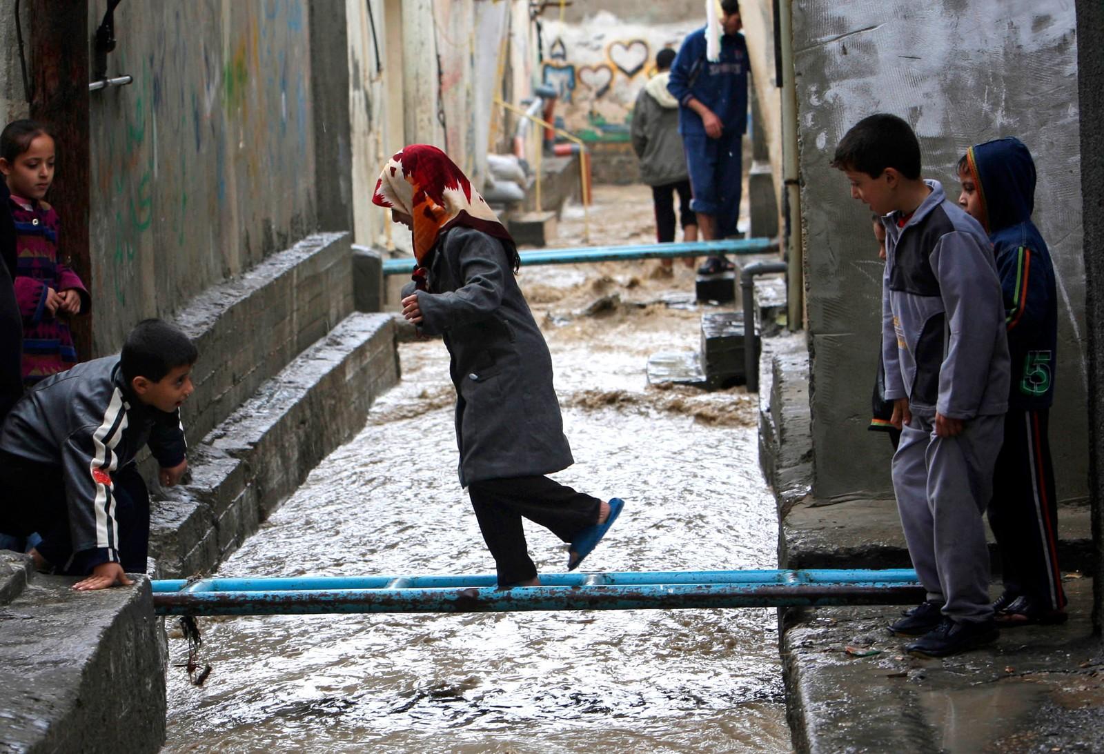 Palestinske barn går over en midlertidig bro etter at en regnstorm.