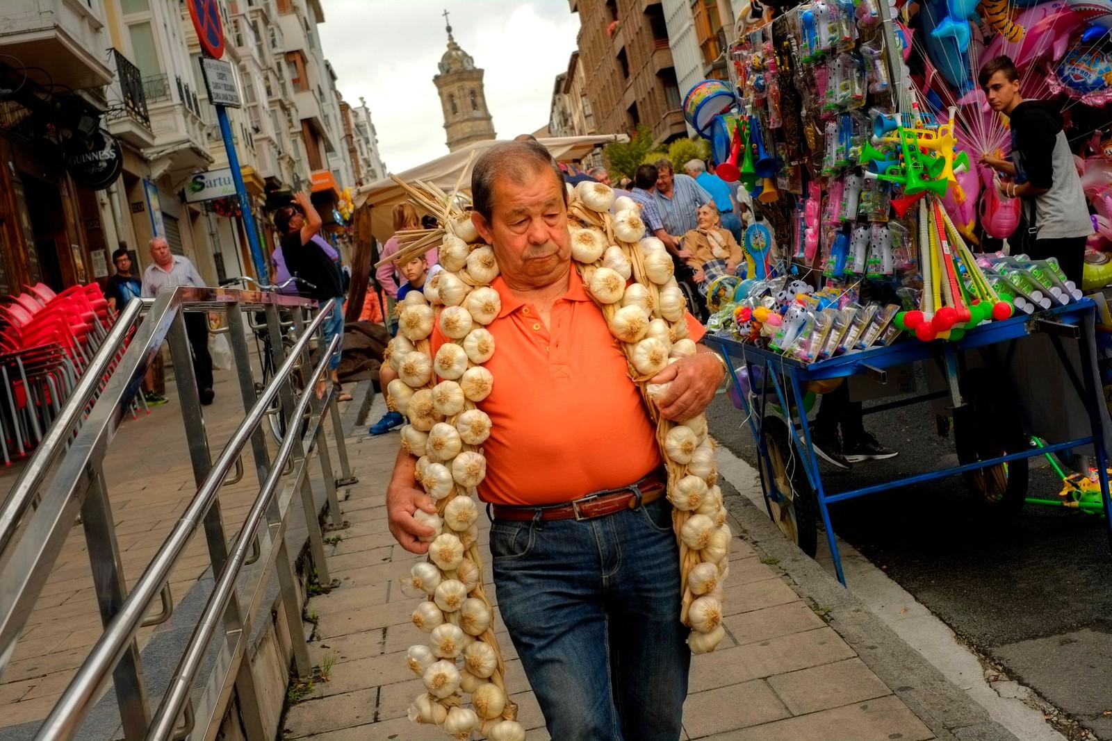 En mann bærer hvitløk i Vitoria i Spania den 25. juli. Hvert år samles hvitløkprodusenter på den tradisjonelle messen, som alltid legges til feiringen av St. Jakobs dag.