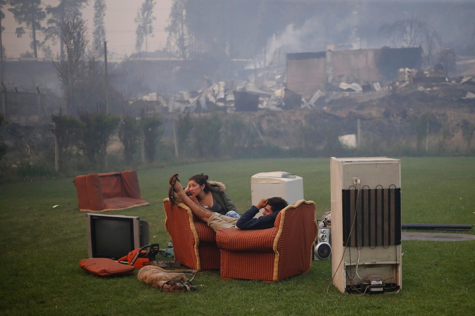 Et ungt par på en fotballbane. En skogbrann forårsaket enorme ødeleggelser og flere dødsfall i Santa Olga i Chile.