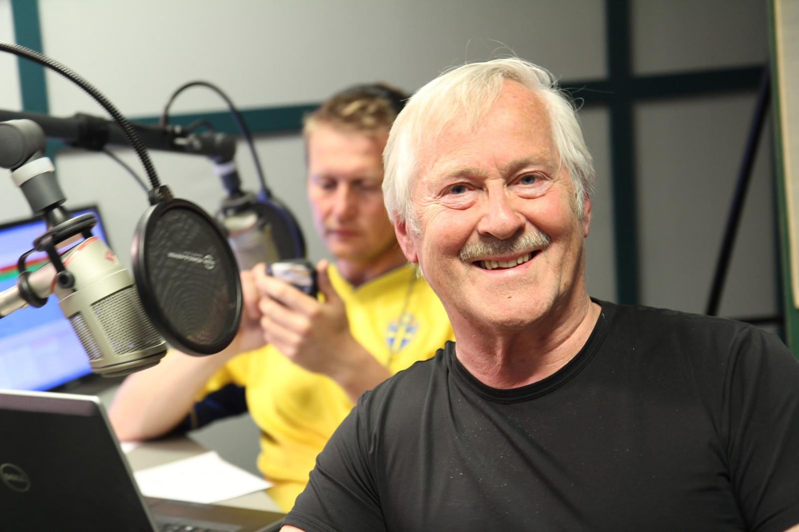NRK-veteran John Skien på plass i studio, med Johan Mihle Laugaland i bakgrunnen.