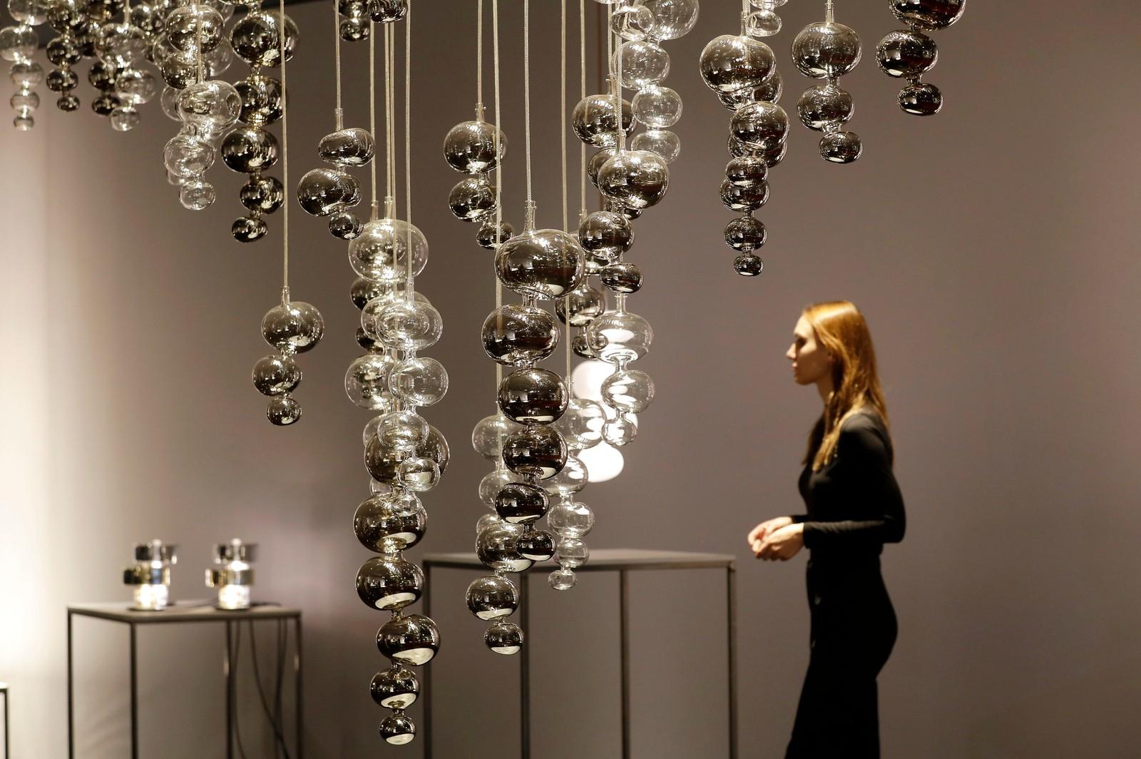 EN kvinne går forbi utsmykninger skapt av Melogranoblus designere på en messe i Milan.
