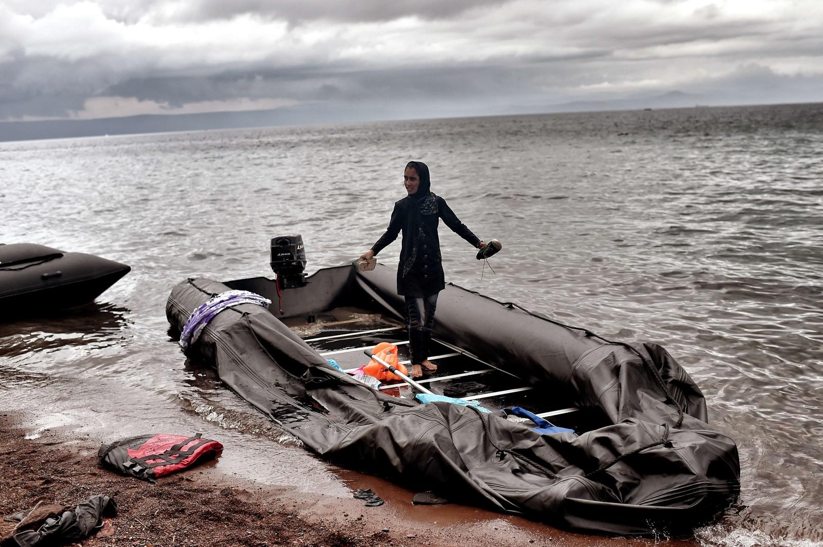 En ung kvinne står barføtt i en ødelagt gummibåt etter å ha ankommet den greske øya Lesbos fra Tyrkia.